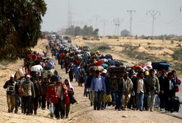 Bangladeshi evacuees walk away from the border after fleeing unrest in Libya