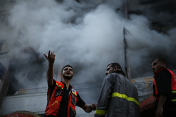 A Palestinian firefighter gestures next to his colleagues as smoke rises out of a building that also houses international media offices, after an Israeli air strike witnessed by a Reuters journalist, in Gaza City