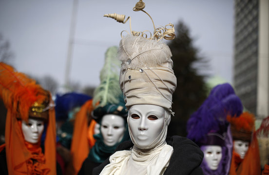 Women wearing masks participate in the International Festival of the Masquerade Games in the town of Pernik