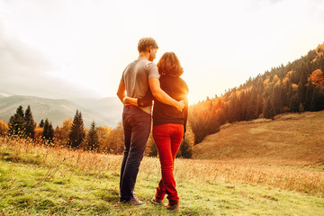 Couple in love tender huge eeach other on the sunset meadow