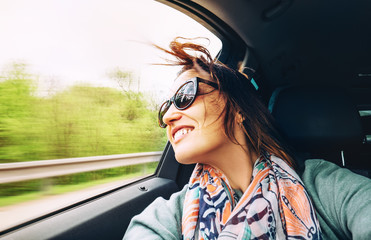 Woman feels free and looks out from open window car