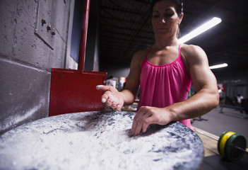 Olympic wrestler Verbeek of Canada chalks up her hands as she lifts weights during her training in Niagra Falls