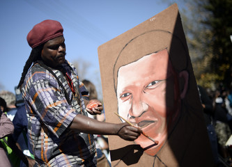 A man paints a portrait of ailing former South African President Nelson Mandela outside the Medi-Clinic Heart Hospital where he is being treated in Pretoria
