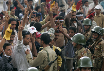 Anti-government protesters flash the victory sign to army soldiers at a barrier blocking a demonstration demanding the ouster of Yemen's President Ali Abdullah Saleh in the southern city of Taiz