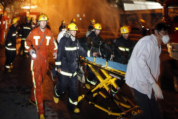 Rescue workers wheel a victim out of a burning building in Shanghai