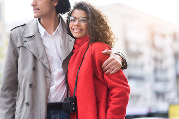 Joyful young woman enjoying hug of boyfriend outdoors