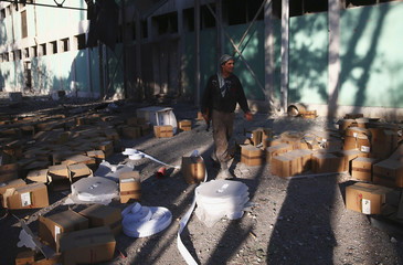 A member of Shabab Al-Huda brigade, operating under Free Syrian Army, walks past boxes at Tameko pharmaceutical factory, after FSA claimed to have taken control of factory, in eastern al-Ghouta,