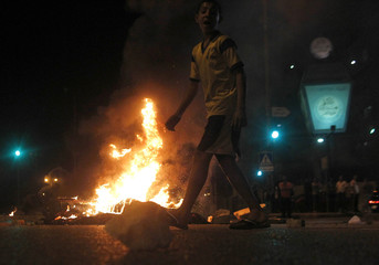 Lebanese Sunni Muslim residents burn tires as they block a main highway in Beirut, to protest the killing of Sheikh Ahmed Abdul Wahid and Muhammed Hussein Miraib