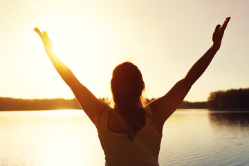 Happy woman enjoying sunset time near water