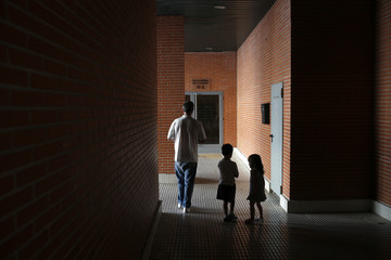 Jorge Blanco walks past children outside the building where they live in Madrid