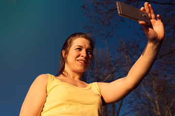 Young woman making selfie picture at sunset time.