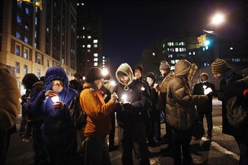 Occupy Wall Street members light candles during a march to honor Rev. Martin Luther King, Jr. in New York