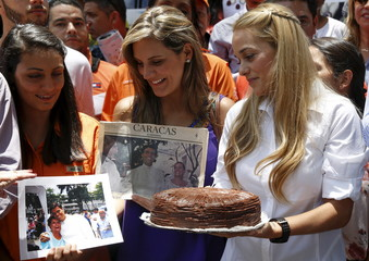 Lilian Tintori, wife of Venezuela's jailed opposition leader Leopoldo Lopez, looks at pictures of him as she carries a cake, during a gathering to celebrate the birthday of her husband in Caracas