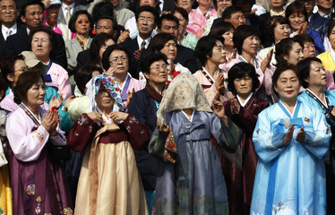 North Korean women cover their heads with handkerchiefs from direct sunlight as they attend a military parade to celebrate the centenary of the birth of North Korea founder Kim Il-sung in Pyongyang