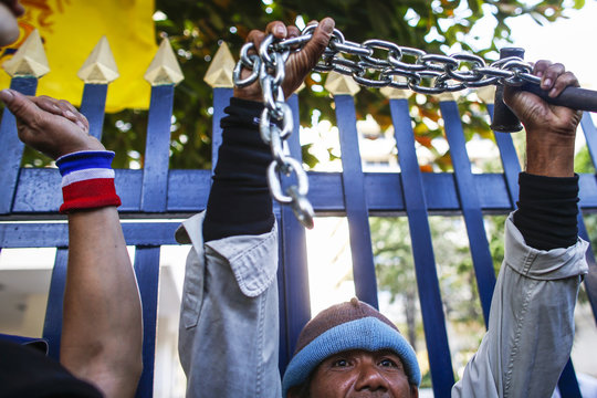 An anti-government protester holds up a chain, used to lock the gates of the Labour Ministry on Monday, during a rally in Bangkok