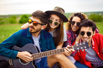 Group of friends enjoying party. The guy plays the guitar. Everyone has a great mood. Summer time.