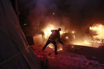 A pro-European protester throws a missile during clashes with Ukranian riot police in Kiev
