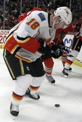 Calgary Flames center Matt Stajan controls the puck against Chicago Blackhawks defenseman Niklas Hjalmarsson in their NHL game in Chicago