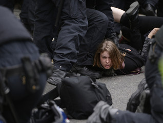 Police officers detain a supporter of a Unite Against Fascism (UAF) counter-demonstration near another protest held by the far-right British National Party (BNP)