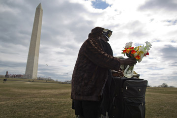 A homeless resident of Washington, repacks a vase of plastic flowers and his other belongings after watching a gathering on the National Mall