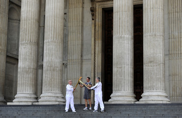Olympic torch bearer John Elbrow receives the flame from Kevin Craig on the steps of St Paul's Cathedral in London