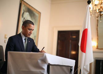 U.S. President Obama writes in the condolence book for Japan's earthquake and tsunami victims at Japan's embassy in Washington