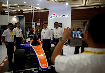Visitors have their picture taken with replica racing car at state-owned oil giant Pertamina's booth at the Indonesia Petroleum Association Convention and Exhibition in Jakarta, Indonesia