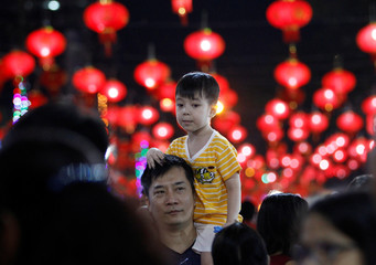 A boy sits on his father's shoulders as they visit the Chinese Lunar New Year's festival in Chinatown, in Yangon