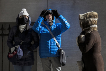Tourists dressed for the cold photograph the New York Stock Exchange in New York's financial district