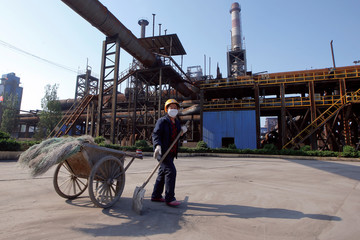 An employee scoops up dust at Shanxi Zhongsheng Iron and Steel in Fenyang