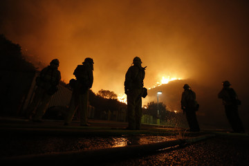 Firefighters battle to protect a CalTrans Maintenance Station and Fuel Depot from the Springs Fire near Pacific Coast Highway and the Los Angeles County Line at Malibu