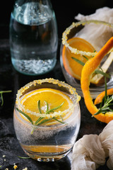 Tonic water cocktail with rosemary and orange. Two glasses and bottle with zest sugar and bubbles over black texture background. Refreshing beverage alco non alcohol. Close up