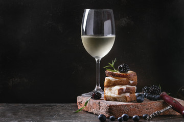 Grilled sandwich with melted goat cheese, blackberry, blueberry, rosemary and honey, served on terracotta board with glass of cold white wine. over dark background. Summer appetizer.