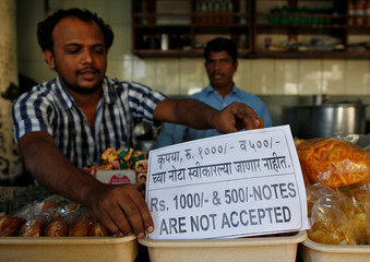 A man puts a notice inside his eatery stall in Mumbai