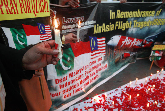 Members of the Lawyers Strategic Council of Pakistan hold up a banner and lit candles during a vigil for the passengers of AirAsia Flight QZ8501 in Lahore