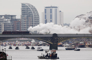 A steam train and pleasure boats from Battersea bridge on the River Thames in London