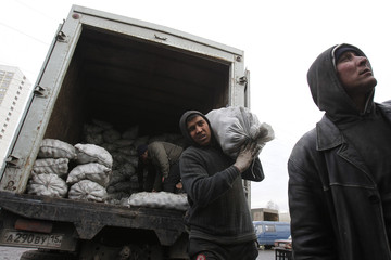 Migrant workers work unload potato sacks at a vegetable market on the outskirts of Moscow