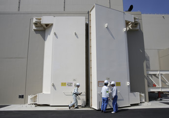 Workers stand in front of a strengthened door at the No.4 reactor building at Chubu Electric Power Co.'s Hamaoka Nuclear Power Station in Omaezaki