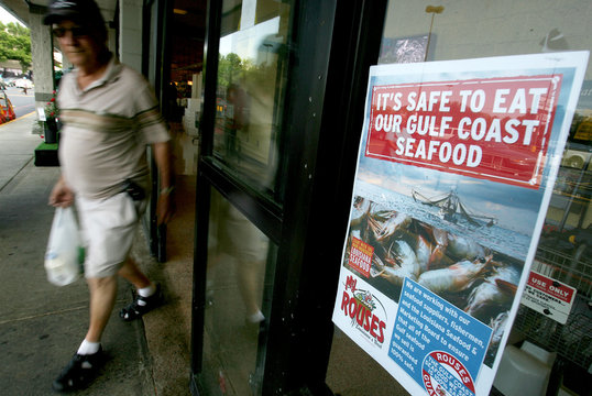 Shopper walks past a sign at a local grocery store in Metairie, Louisiana advertising safe seafood from the Gulf Coast