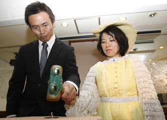 """Tomoharu and Miki Saito use a hammer to smash their wedding ring during a """"divorce ceremony"""" in Tokyo"""