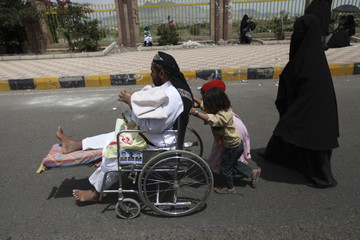 Children push a man in a wheelchair after the weekly Friday prayers during a rally to demand the prosecution of the family of former Yemeni President Saleh in Sanaa