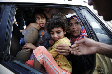 Palestinians flee in a vehicle from Israeli shelling in Bet Lahiya in northern Gaza Strip
