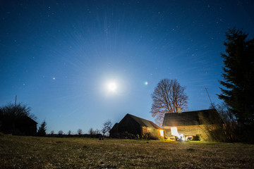 Overhead milky way with stars in clear summer night. Old barn house. Country side.