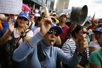 An opposition supporter hits a pot during a protest in Caracas