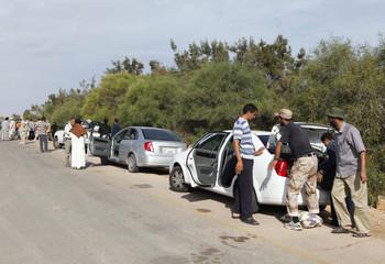 Anti-Gaddafi fighters search through passenger vehicles ferrying families fleeing Sirte and headed towards Khamseen Gate