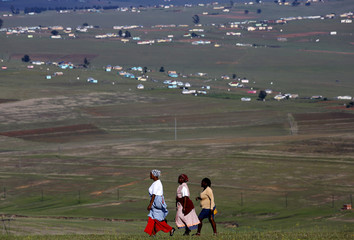 Local women walk to a public viewing point near the burial ground of late former South African President Nelson Mandela ahead of his funeral in Qunu