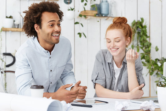 Teamwork and cooperation. Handsome attractive unshaven dark-skinned male designer having fun during break at office, telling jokes and laughing, his cute redhead woman colleague smiling next to him