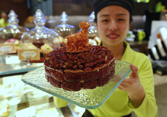 A waitress poses with a cake decorated with a goat-shaped chocolate to celebrate the upcoming Chinese Lunar New Year, during a photo opportunity at a bakery of Kerry Hotel in Beijing