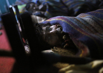 A homeless man covered in a blanket looks on inside a government-run night shelter on a cold winter night in the old quarters of Delhi