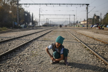 A child plays along railway tracks a makeshift camp for migrants and refugees at the Greek-Macedonian border near the village of Idomeni